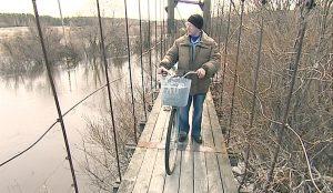 Переходить и даже переносить провизию местным жителям приходится по старому подвесному мосту