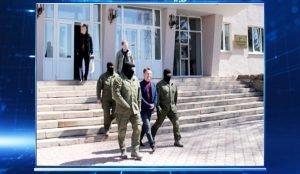 Геннадий Васьков выходит из здания в сопровождении людей в камуфляже